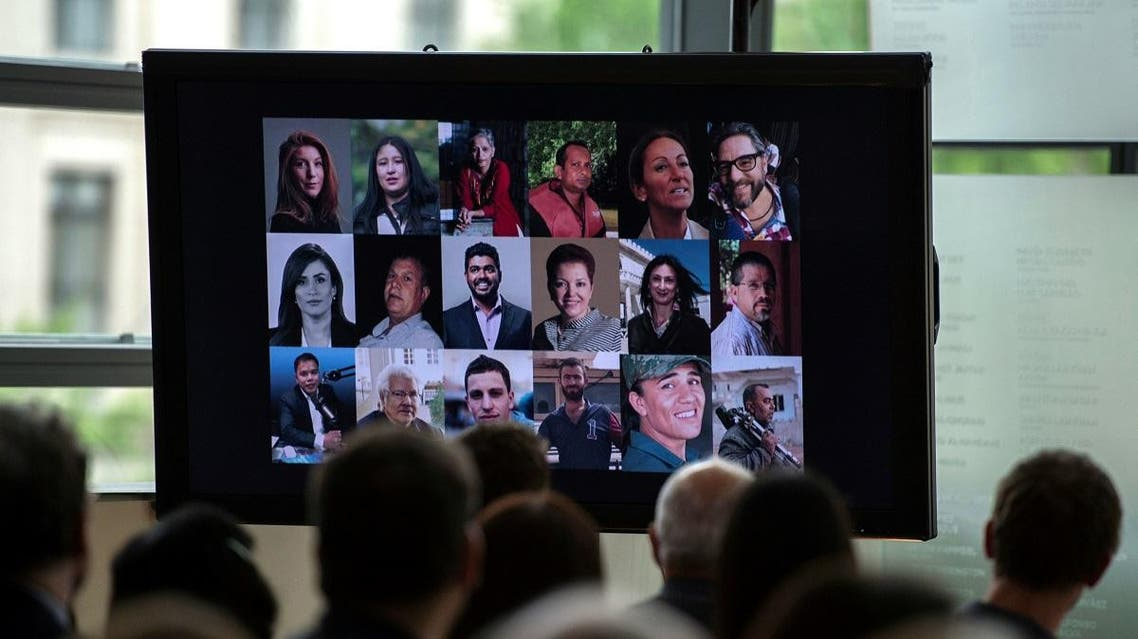 People look at a video showing the journalists killed in 2017 during a memorial event at the Newseum in Washington, DC on June 4, 2018. (AFP)
