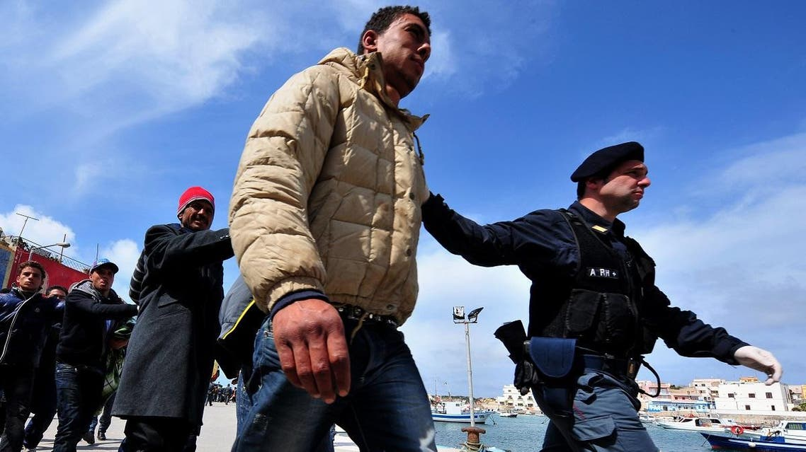 Policemen escort Tunisians would-be immigrants who are waiting to be identified on the Italian island of Lampedusa. (AFP)