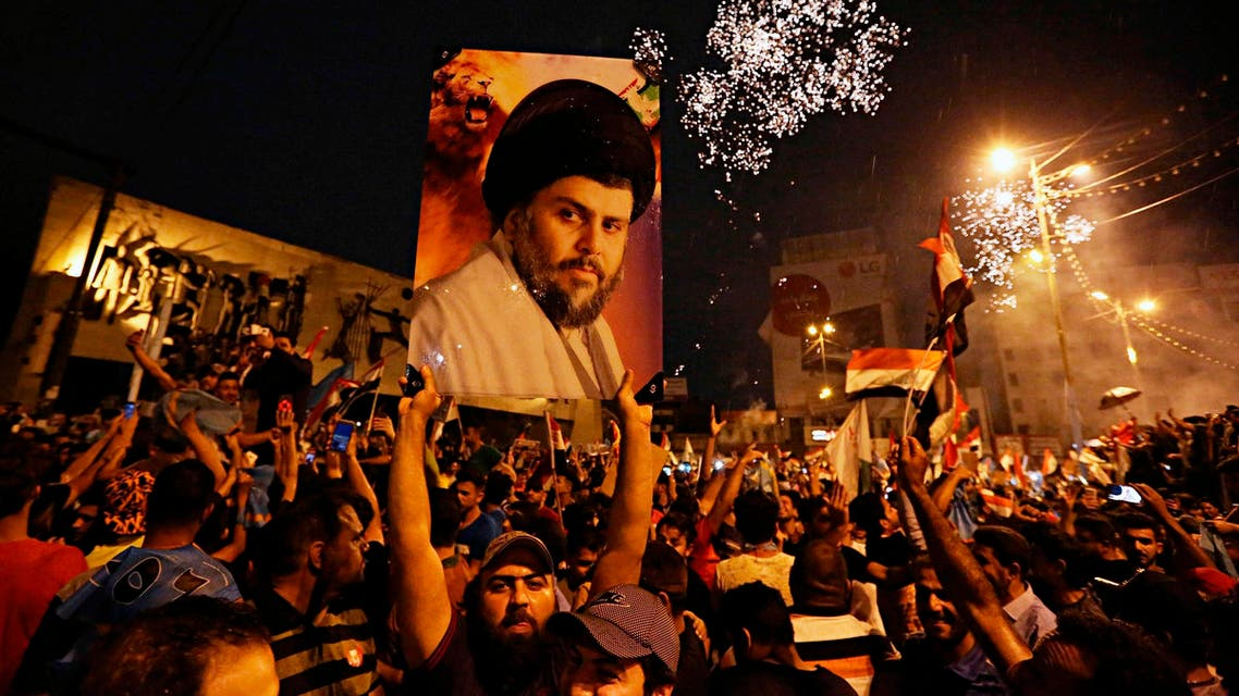 Supporters of Muqtada al-Sadr carry his image as they celebrate in Tahrir Square, Baghdad, on May 14, 2018. (AP)