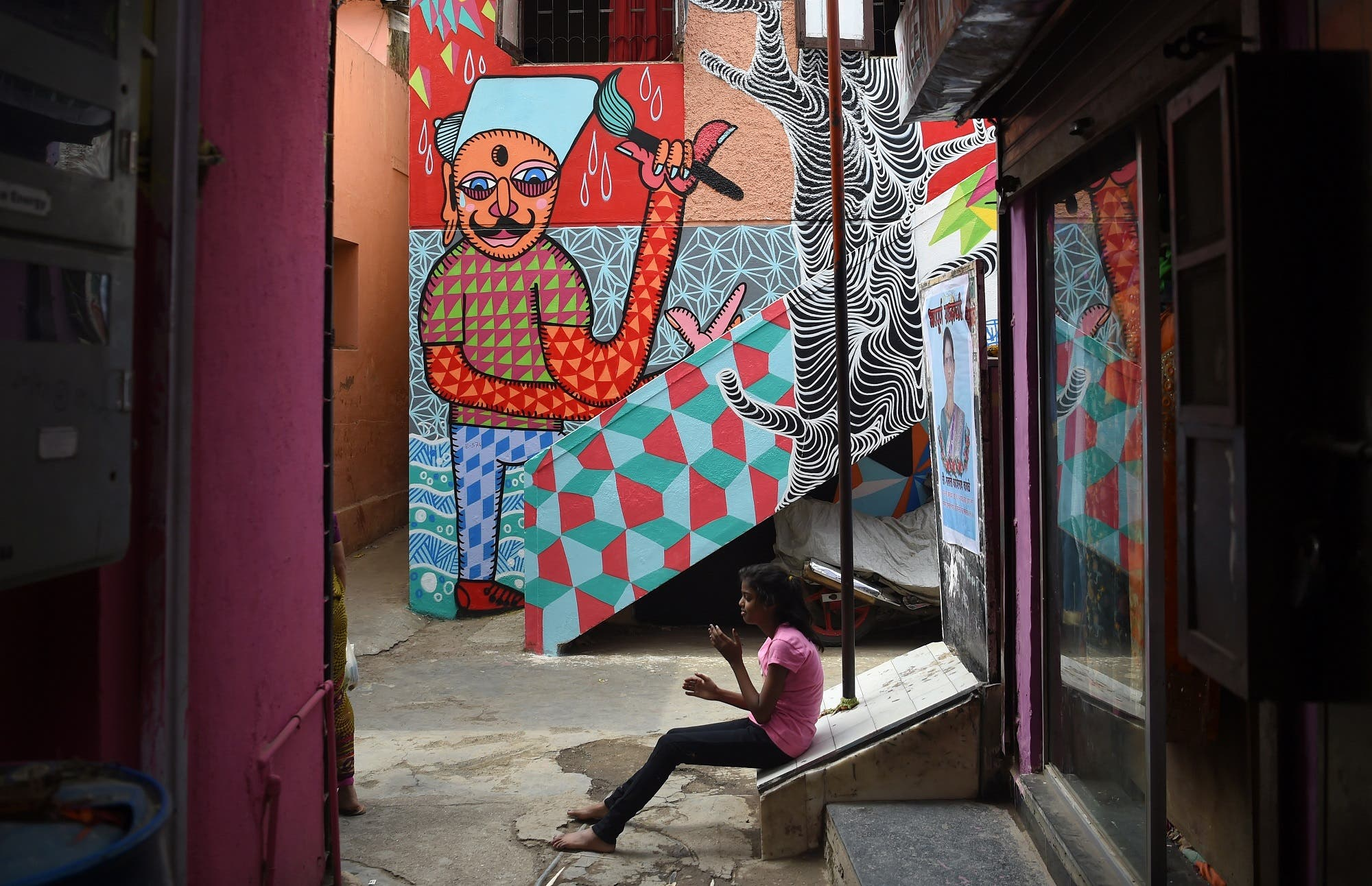 In this picture taken on June 1, 2018, an Indian girl sits near a mural in Mumbai. (AFP)