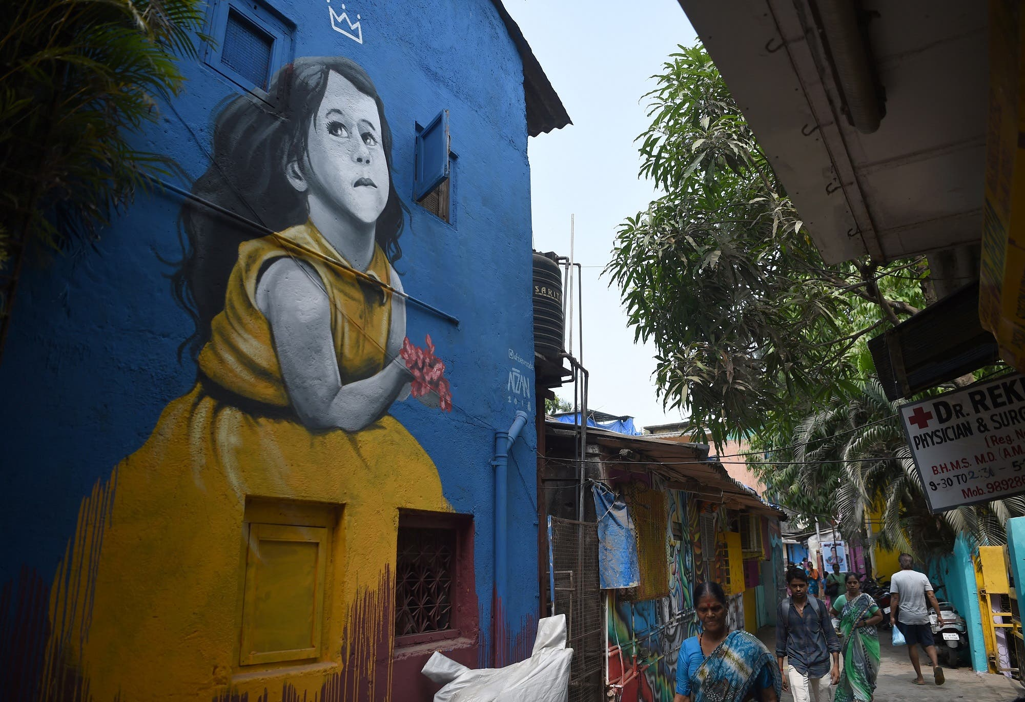 Residents walk past a mural in Mumbai on June 1, 2018. (AFP)