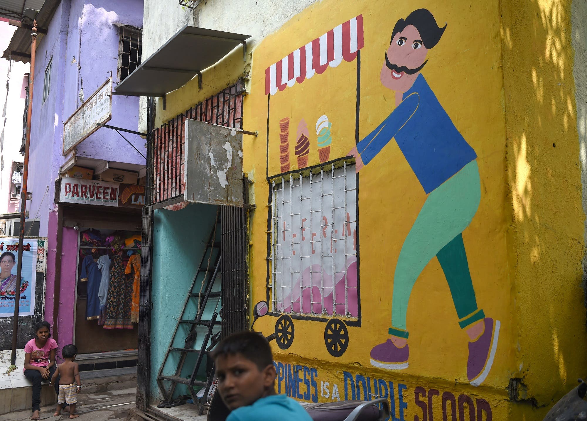 In this picture taken on June 1, 2018, Indian children stroll near a mural in Mumbai. (AFP)