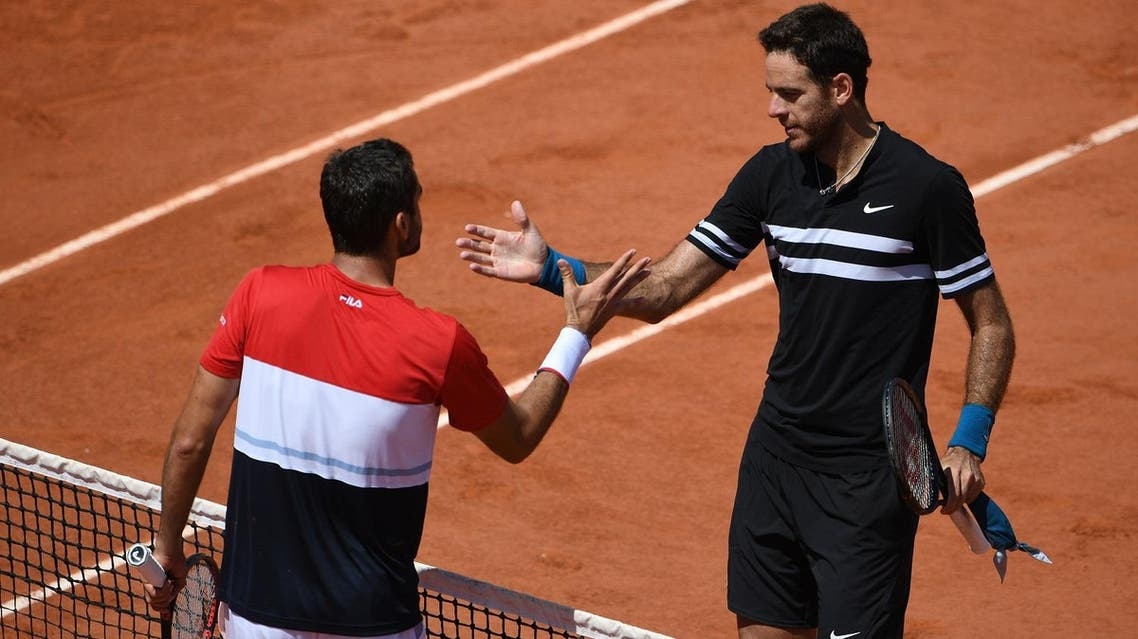 Juan Martin del Potro (R) is congratulated by  Marin Cilic after winning, at the end of their men's singles quarter-final match at the French Open in Paris on June 7, 2018.  (AFP)