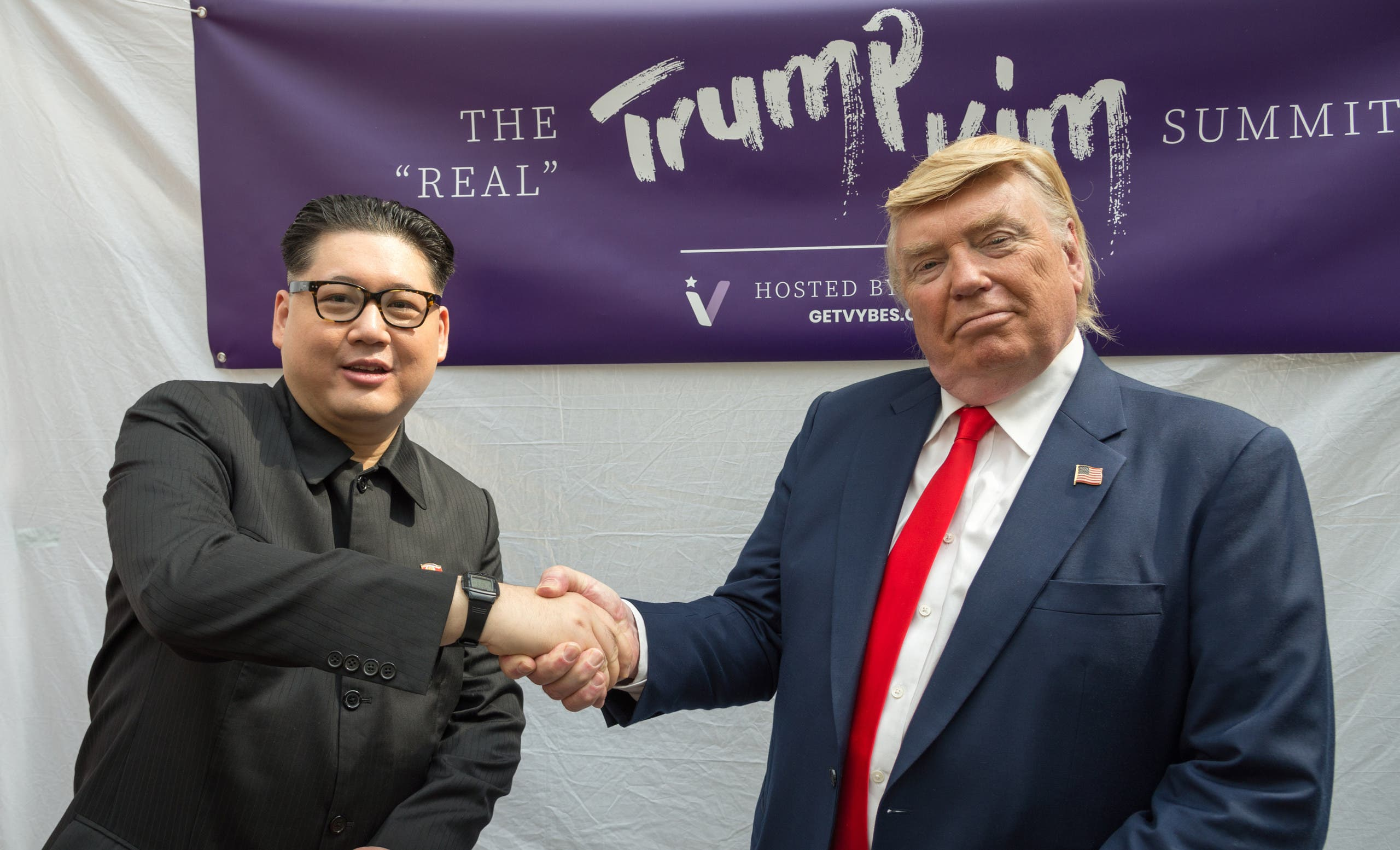 Kim Jong Un and Donald Trump impersonators Howard X (L) and Dennis Alan (R) shakes hands during a promotional event on June 9, 2018 in Singapore. (AFP)