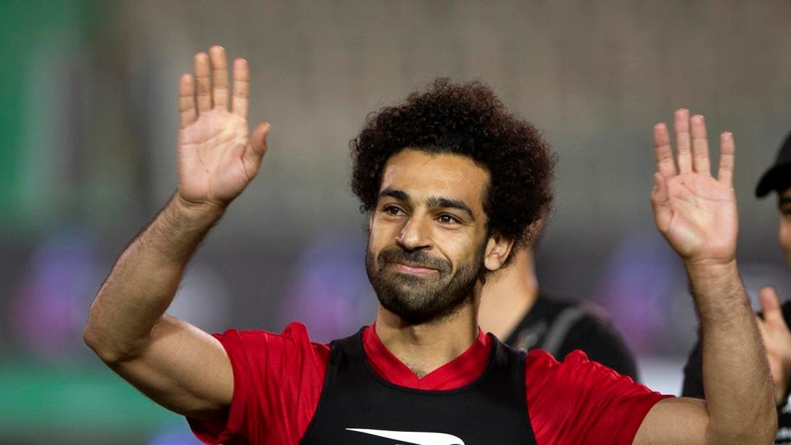 Egyptian national team soccer player and Liverpool's star striker Mohammed Salah smiles as he greets fans during the final training of the national team at Cairo Stadium in Cairo. (AP)