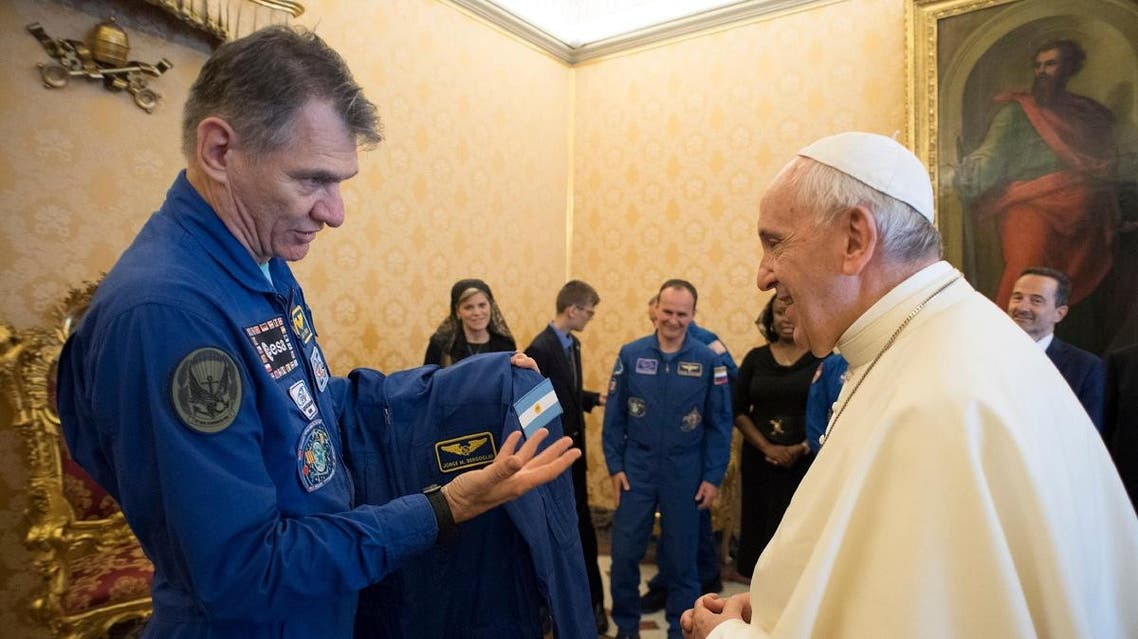 Pope Francis receives an astronaut suit from Italian astronaut Paolo Nespoli during a private meeting with crew members of the ISS 53 space mission at the Vatican. (Reuters)