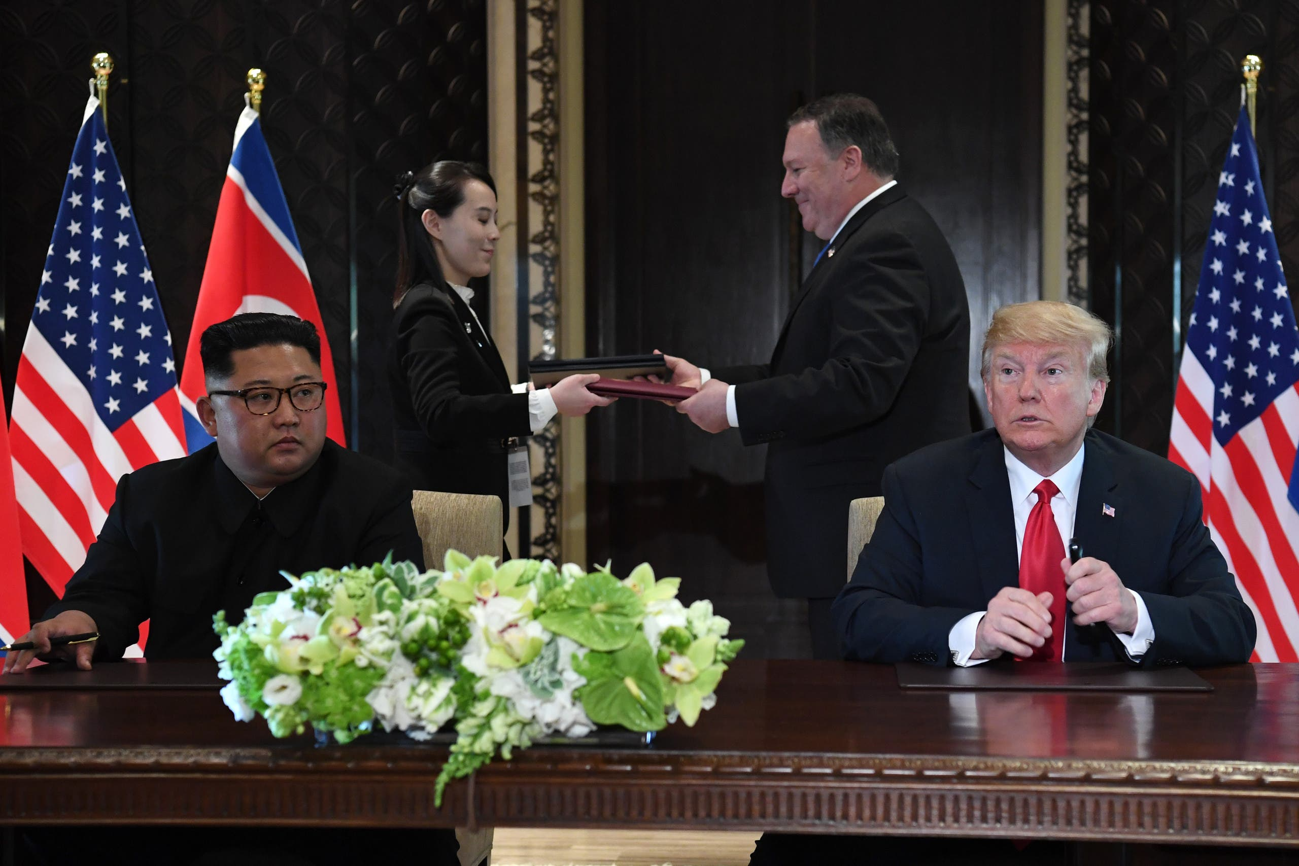 US President Donald Trump (R) and North Korea's leader Kim Jong Un (L) look on as documents are exchanged between US Secretary of State Mike Pompeo (2nd R) and the North Korean leader's sister Kim Yo Jong (2nd L) at a signing ceremony during their historic US-North Korea summit, at the Capella Hotel on Sentosa island in Singapore on June 12, 2018. (AFP)