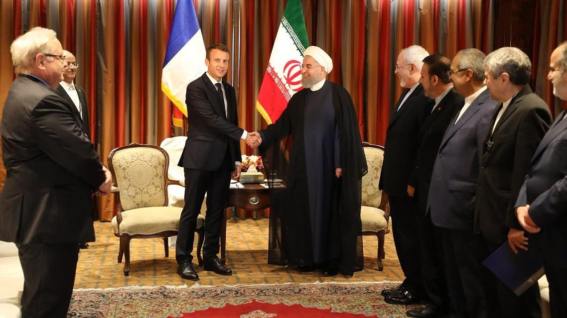 Macron (C-L) shakes hands with his Iranian counterpart Hassan Rouhani as Iran's foreign minister, Mohammad Javad Zarif (5th R) and other members of the Iranian delegation (R) stand next to them during an official meeting. (AFP)