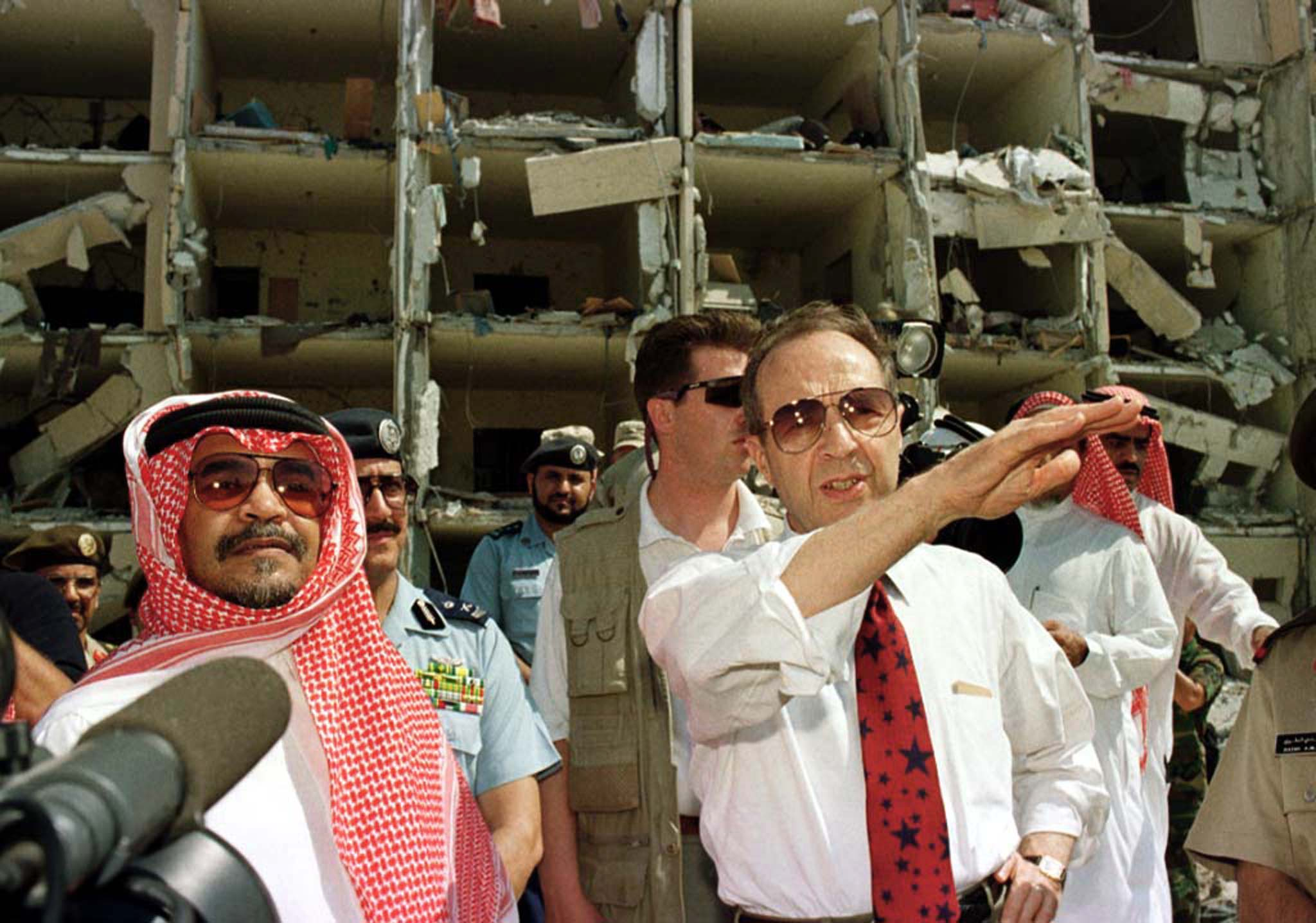 US Secretary of Defence William Perry (R), accompanied by the Saudi Ambassador to the US, Prince Bandar bin Sultan bin Abd al-Aziz Al Saud (L), survey the bomb site outside the heavily damaged apartment at the Khobar Towers housing complex in Dhahran June 29. (Reuters)
