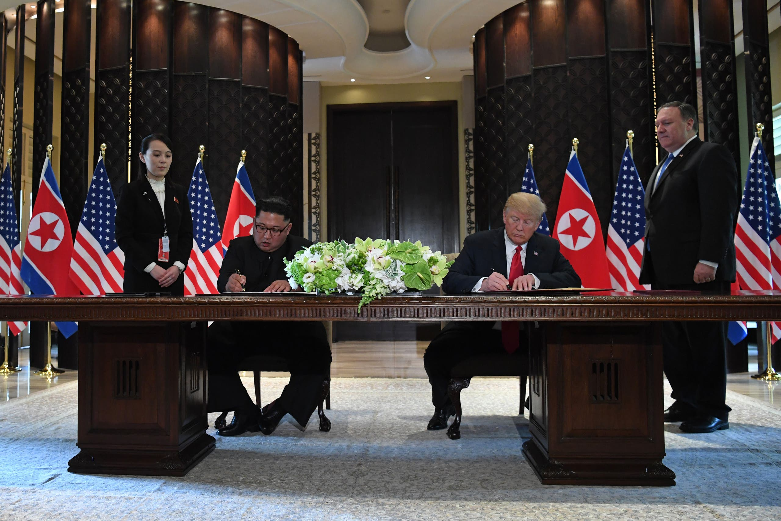 US President Donald Trump (2nd R) and North Korea's leader Kim Jong Un (2nd L) sign documents as US Secretary of State Mike Pompeo (R) and the North Korean leader's sister Kim Yo Jong (L) look on at a signing ceremony during their historic US-North Korea summit, at the Capella Hotel on Sentosa island in Singapore on June 12, 2018. (AFP)