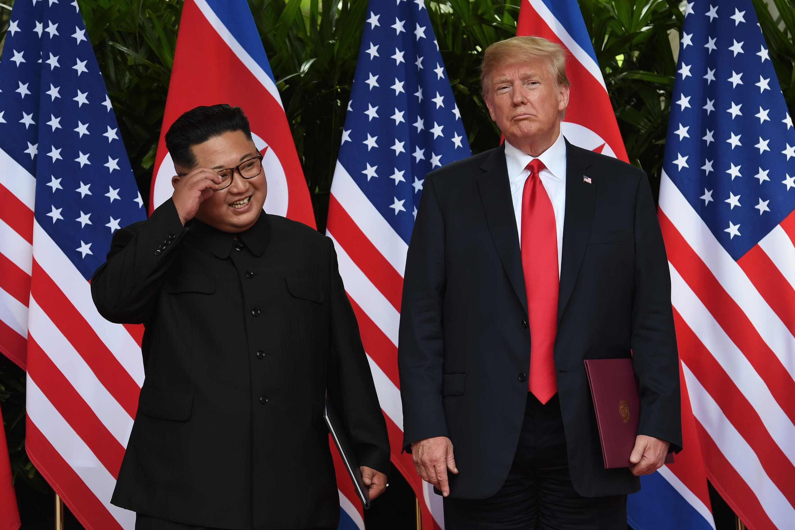 North Korea's leader Kim Jong Un (L) poses with US President Donald Trump (R) after taking part in a signing ceremony at the end of their historic US-North Korea summit, at the Capella Hotel on Sentosa island in Singapore on June 12, 2018. Donald Trump and Kim Jong Un became on June 12 the first sitting US and North Korean leaders to meet, shake hands and negotiate to end a decades-old nuclear stand-off. (AFP)