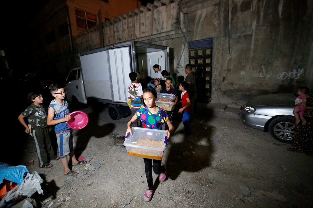 Children help volunteers of initiative, Family Kitchen, to transfer excess food from five-star hotels before redistributing them to underprivileged families in Al-Baqaa Palestinian refugee camp, near Amman. (Reuters)
