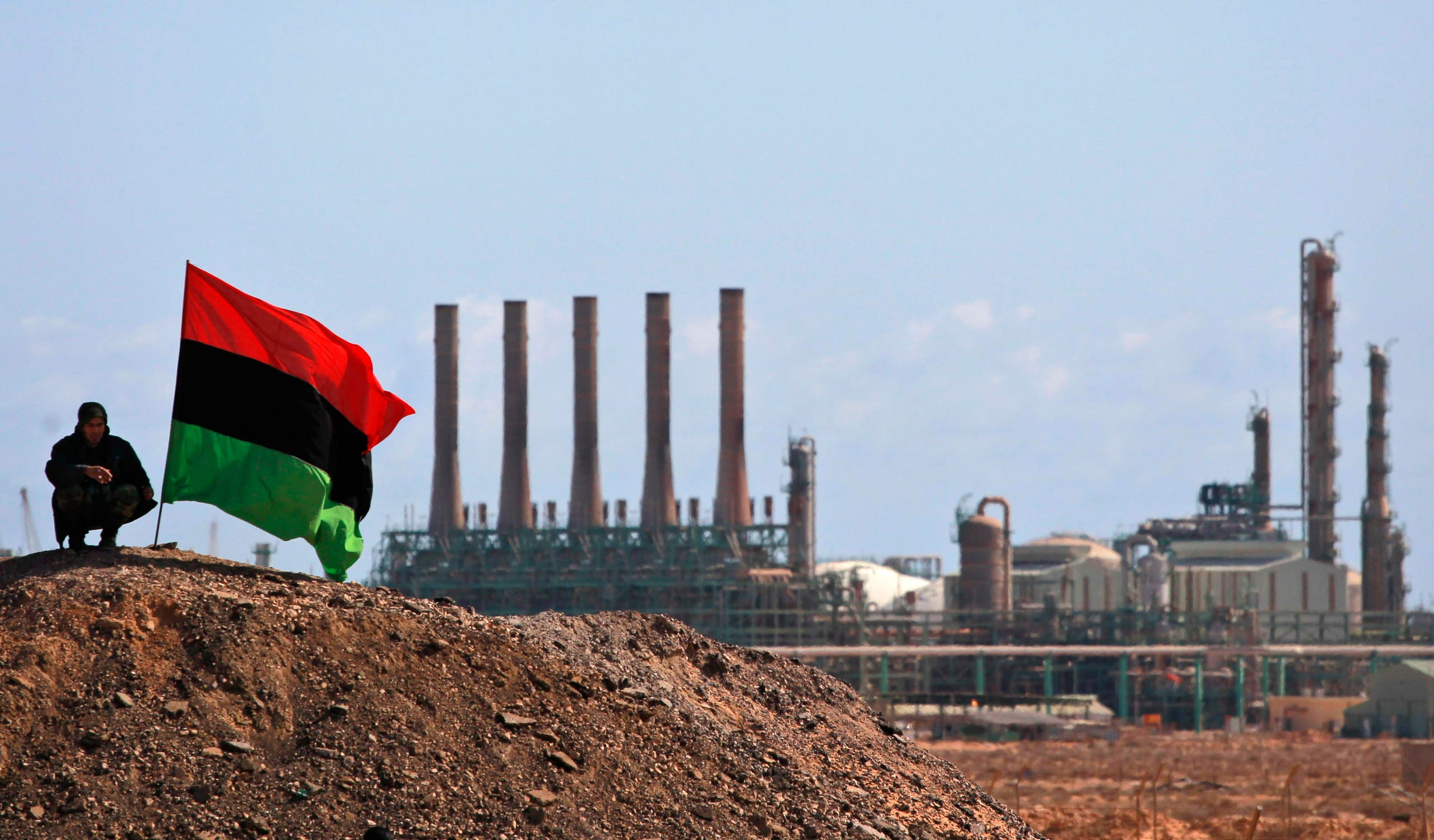 A Libyan rebel who is part of the forces against Libyan leader Moammar Gadhafi sits next to a pre-Gadhafi flag as he guards outside the refinery in Ras Lanuf, eastern Libya. (File Photo: Reuters)