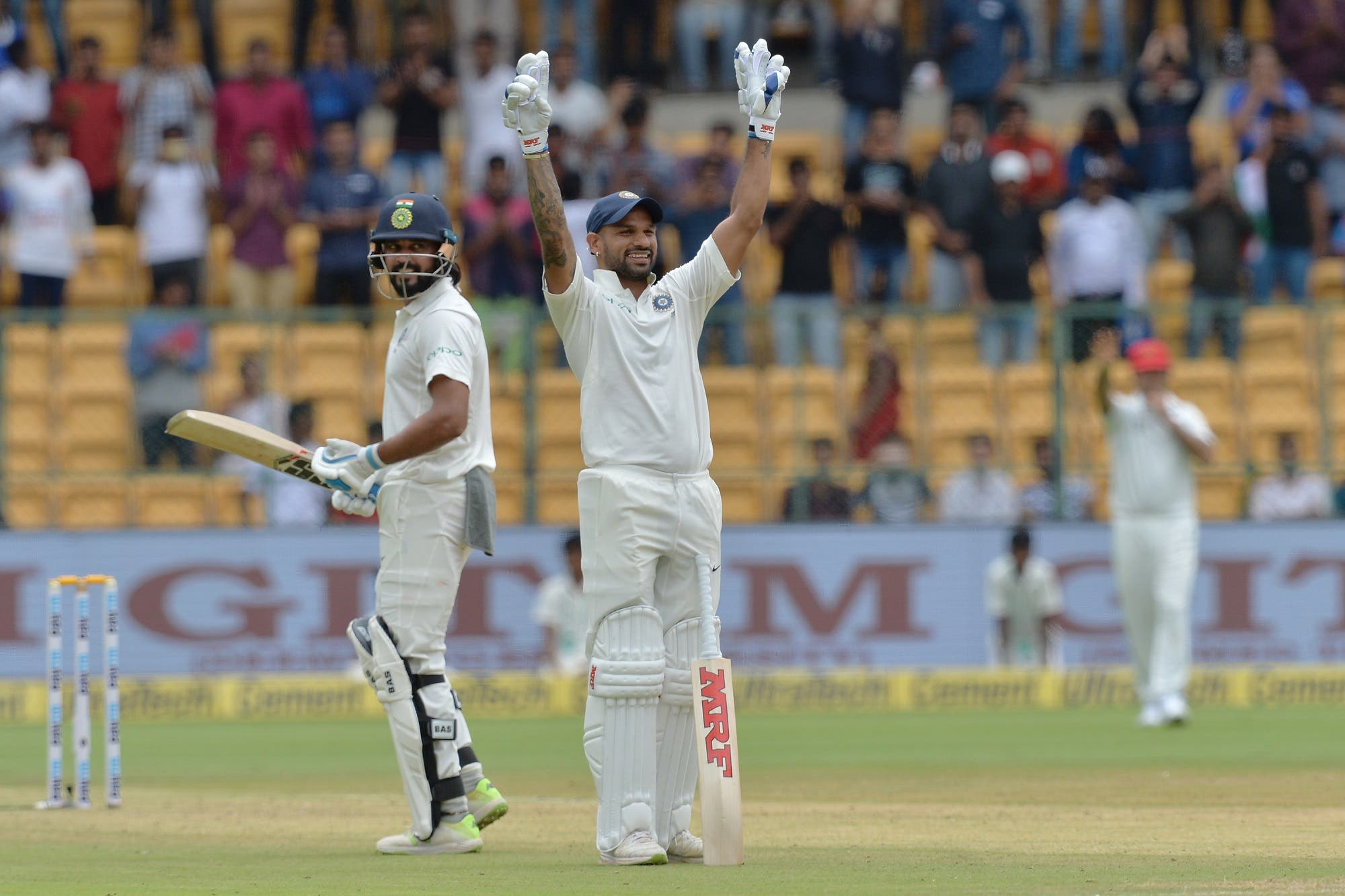 Indian cricketer Murali Vijay (L) looks on as teammate Shikhar Dhawan (C) celebrates his century (100 runs) during the first day of the one-off cricket Test match between India and Afghanistan in Bangalore on June 14, 2018. (AFP)