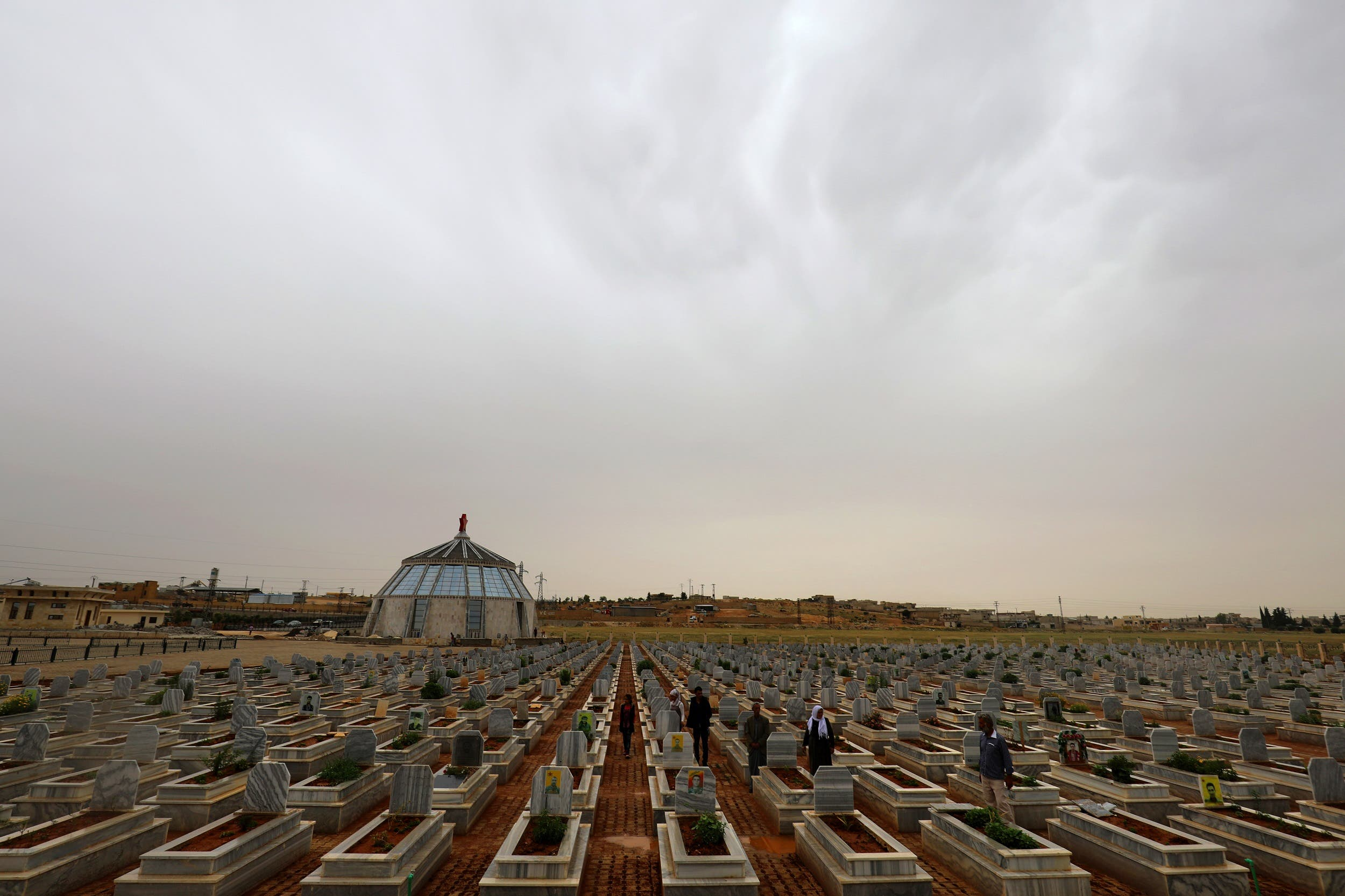 Syrian Kurds visit on May 28, 2018 the tombs of loved ones at a cemetery in Kobane. (AFP)