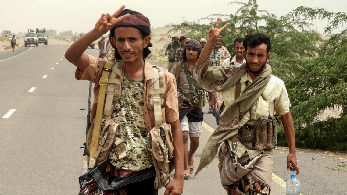 Yemeni pro-government forces flash the victory gesture as they arrive in al-Durayhimi district, about nine kilometres south of Hodeidah international airport on June 13, 2018. (AFP)