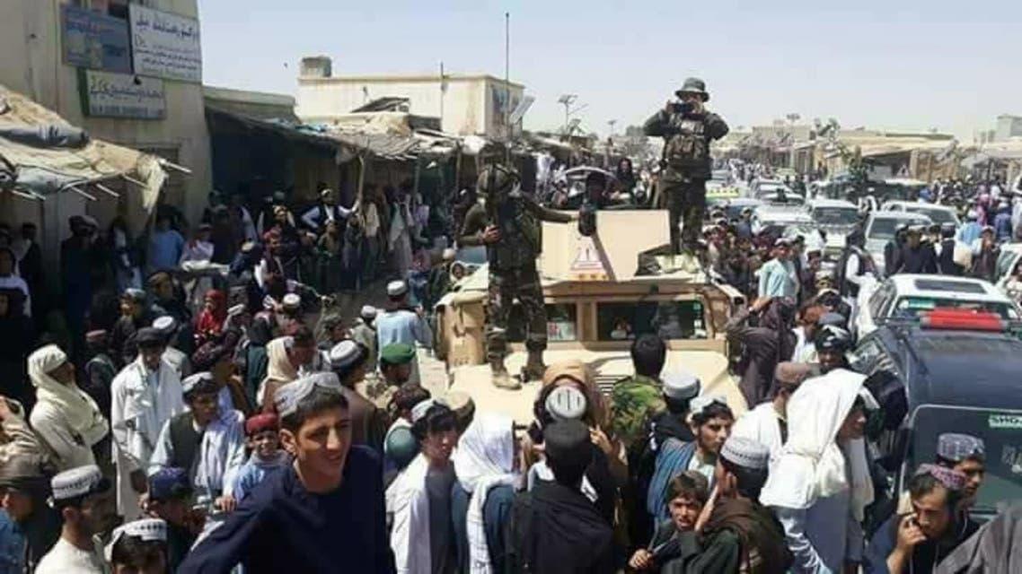 عناصر طالبان يجتمعون حول سيارة عسكرية حكومية