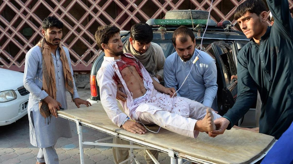 Afghan volunteers carry an injured man on a stretcher to an hospital following a suicide bomber blew himself in Jalalabad. (AFP)