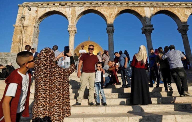 Palestinian Muslim worshippers take pictures as they gather for the morning Eid al-Fitr prayer near the Dome of Rock at the Al-Aqsa Mosque compound, Islam's third most holy site, in the Old City of Jerusalem on June 15, 2018. (AFP)