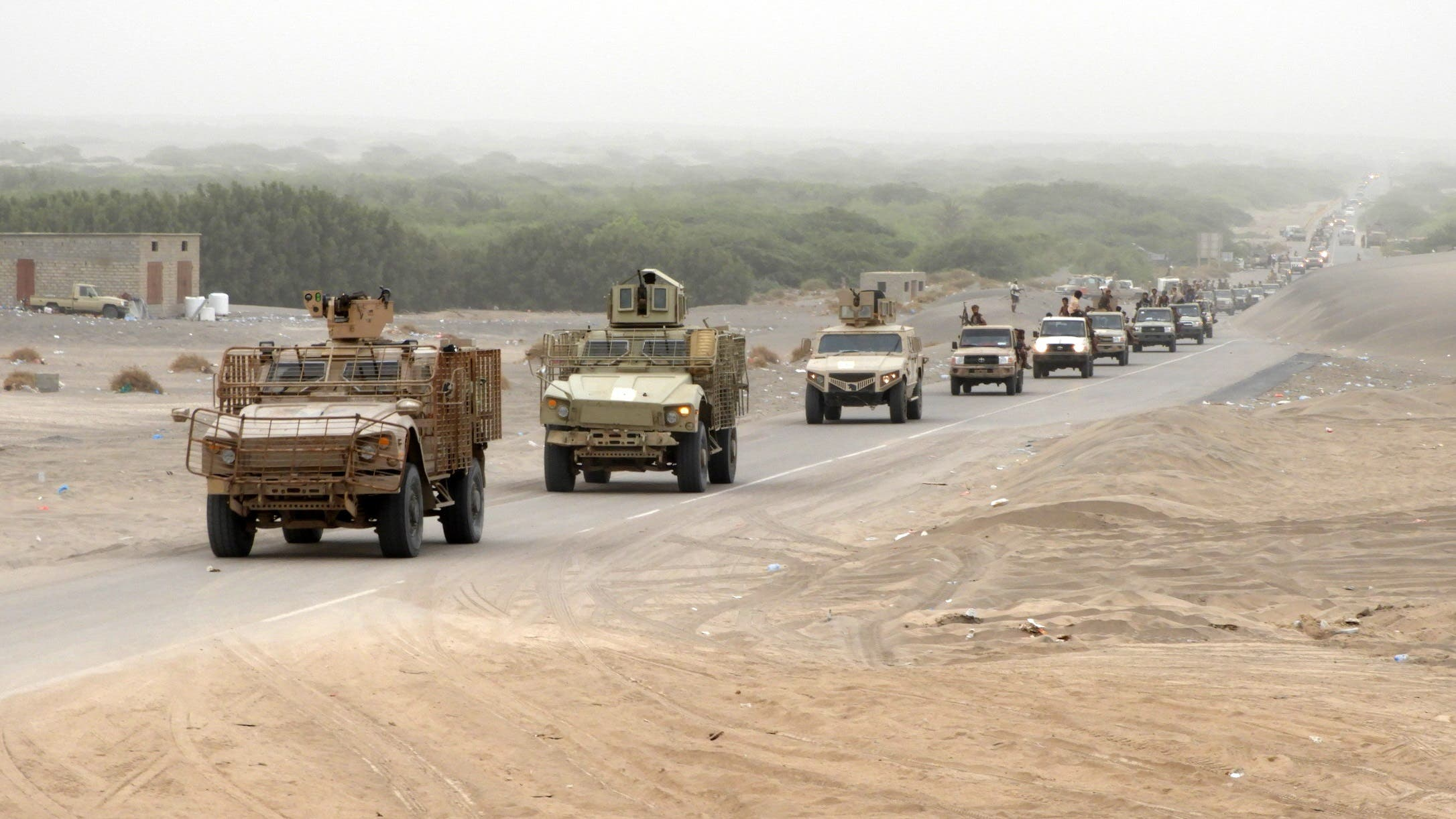 A column of Yemeni pro-government forces and armoured vehicles arrives in al-Durayhimi district, about nine kilometres south of Hodeidah international airport on June 13, 2018. (AFP)