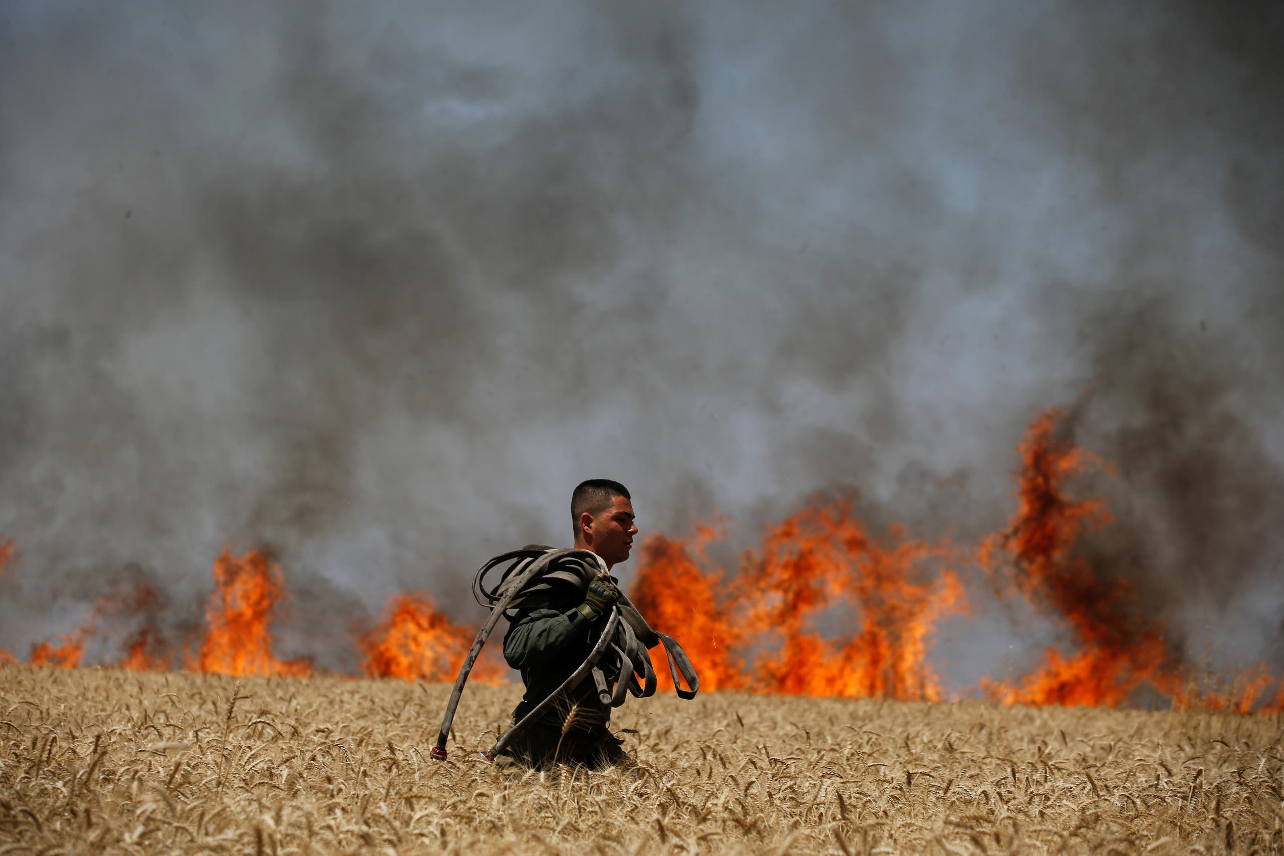 An Israeli soldier carries a hose as he walks in a burning field on the Israeli side of the border fence between Israel and Gaza near kibbutz Mefalsim, Israel. (Reuters)