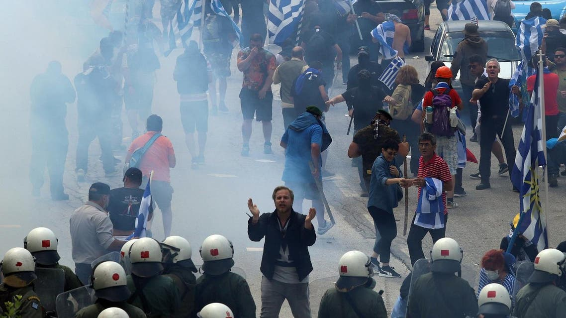 Protestors holding Greek flags walk amid smoke during a protest at the village of Pisoderi near the border with Macedonia in northern Greece on July 17, 2018. (AFP)