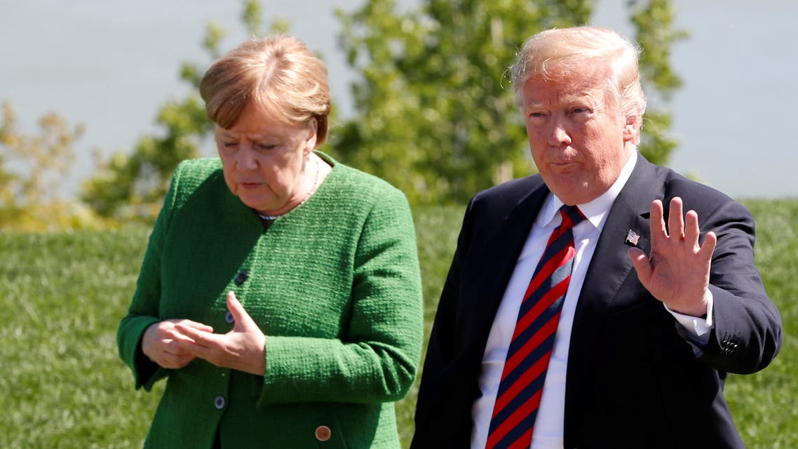 FILE PHOTO: German Chancellor Angela Merkel stands next to U.S. President Donald Trump while posing with other leaders (not pictured) for a family photo at the G7 Summit in the Charlevoix city of La Malbaie, Quebec, Canada, June 8, 2018. REUTERS/Yves Herman/File Photo