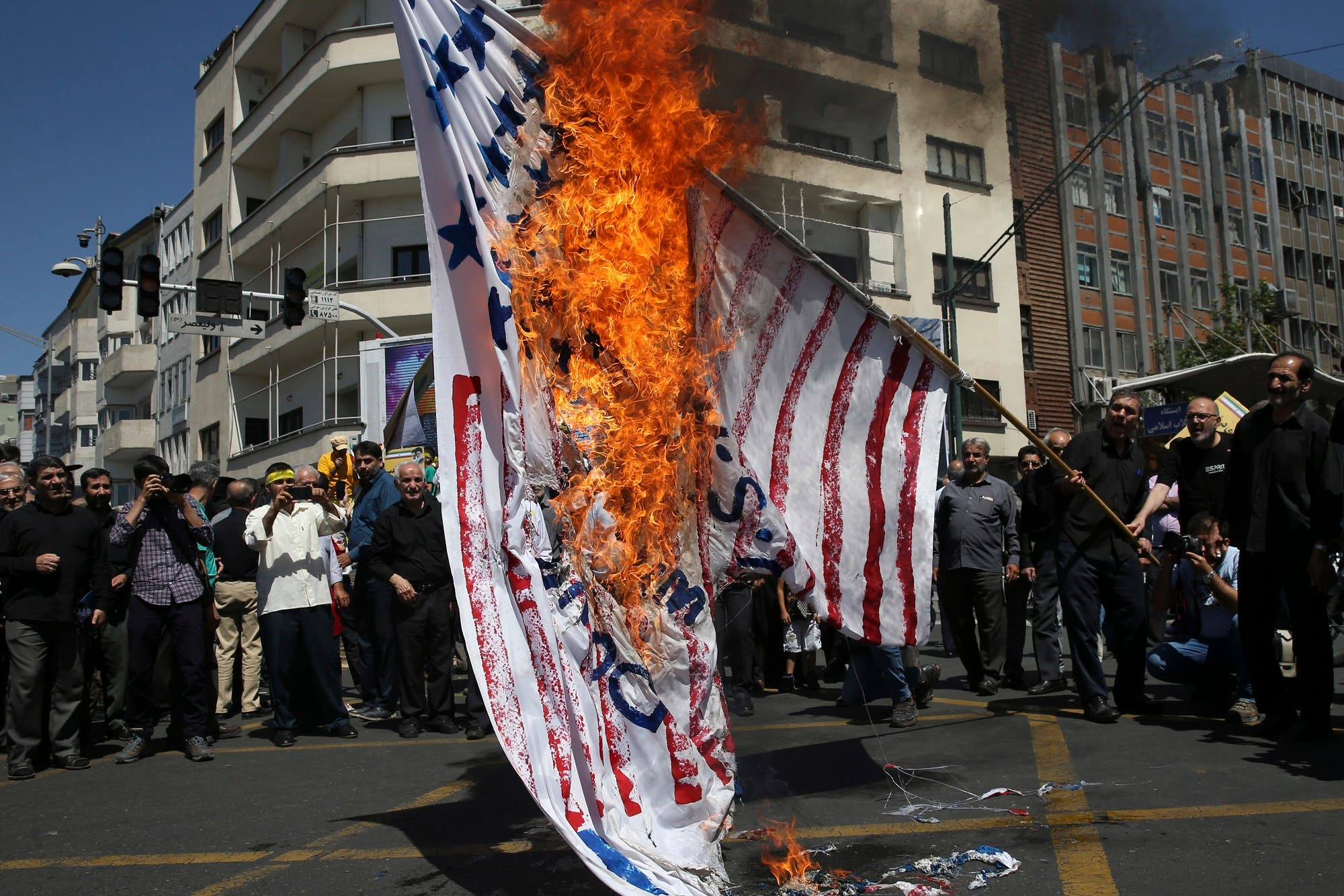 Iranian protesters burn a representation of the US flag at a rally in Tehran on June 8, 2018. (AP)