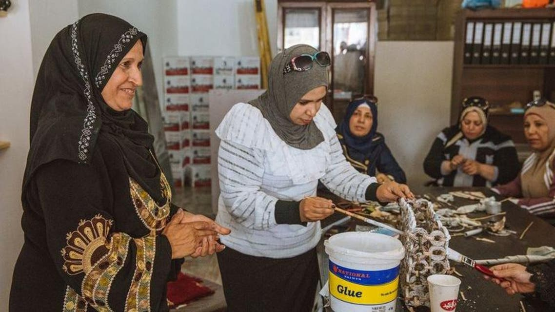 Syrian refugee Sameera Al Salam shows a colleague how to strengthen a paper handbag with glue, at an up-cycling workshop in Irbid city, northern Jordan, May 9, 2018. (Photo: Freya Dowson/Action Against Hunger)
