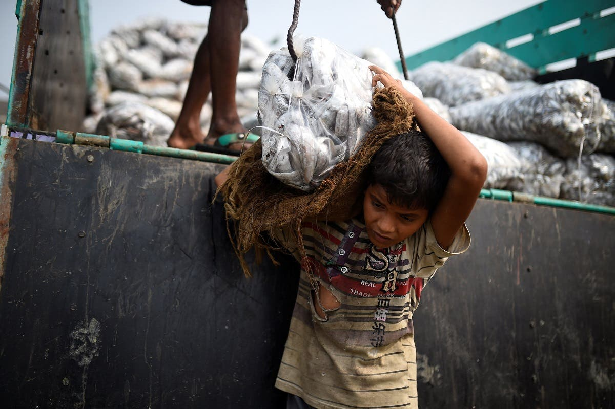 Rohingya refugee Asma Akter, 10, lifts bags of frozen fish from a delivery truck at Nazirartek fish drying yard in Cox's Bazar, Bangladesh. (Reuters)