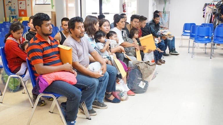 Edilberto Garcia, (2nd from the left) who was separated from his 17 year old son after traveling from Honduras, sits among other migrants soon after arriving at a humanitarian center in the border town of McAllen, Texas on June 14, 2018. (AFP)