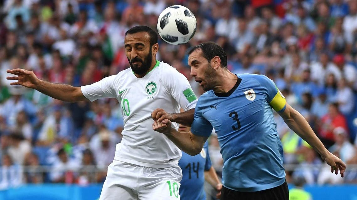 Saudi  forward Mohammed Al-Sahlawi (L) vies with Uruguay's defender Diego Godin during the Russia 2018 World Cup Group A football match on June 20, 2018.  (AFP)