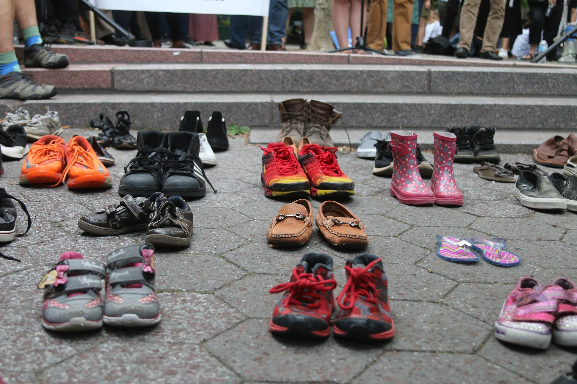 Around the stage, pairs of shoes were lined up to represent asylum-seekers who have crossed borders by land. (Supplied)