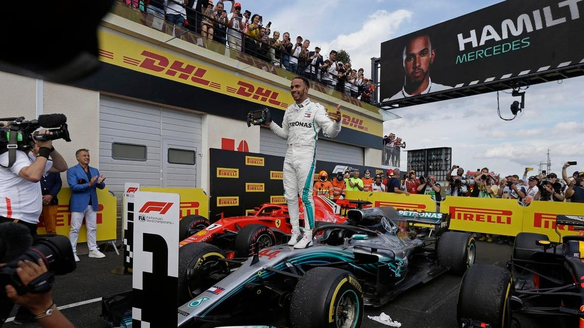 Mercedes driver Lewis Hamilton of Britain celebrates while standing on his car after winning the French Formula One Grand Prix  (AP)