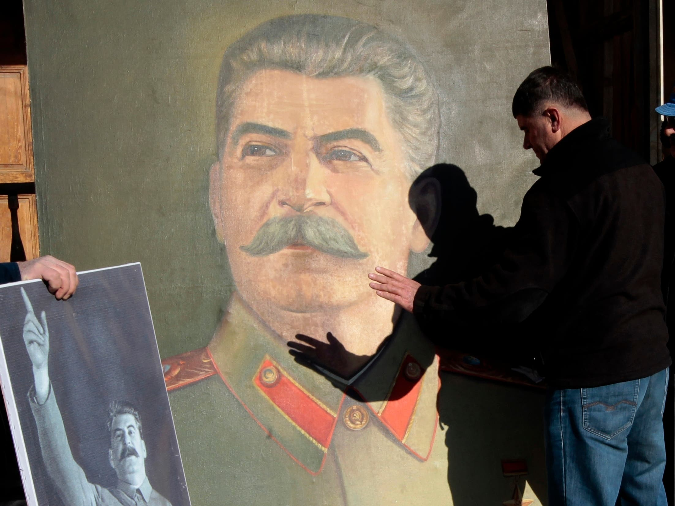 A Georgian man plays with a shadow on a portrait of Soviet dictator Joseph Stalin, during a rally marking Stalin's birthday in his home town of Gori, some 80 km (50 miles) west of the Georgian capital Tbilisi. (AP)