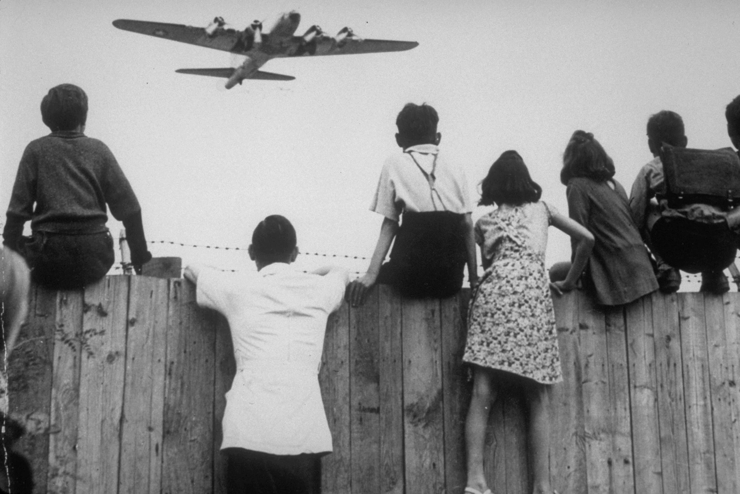 West Berlin children perched on the fence of Tempelhof airport watch the fleets of U.S. airplanes bringing in supplies in 1948 to circumvent the Russian blockade of land and waterways. (AP)