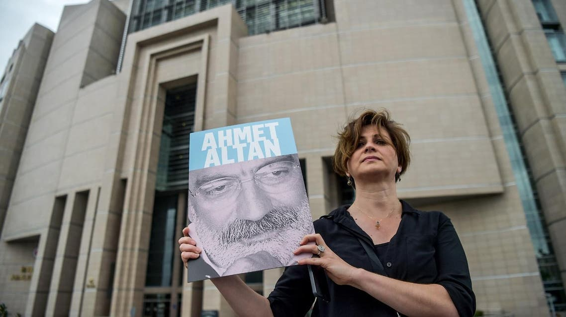 A journalist poses with a portrait of Ahmet Altan in front of the Istanbul courthouse on June 19, 2017. (AFP)