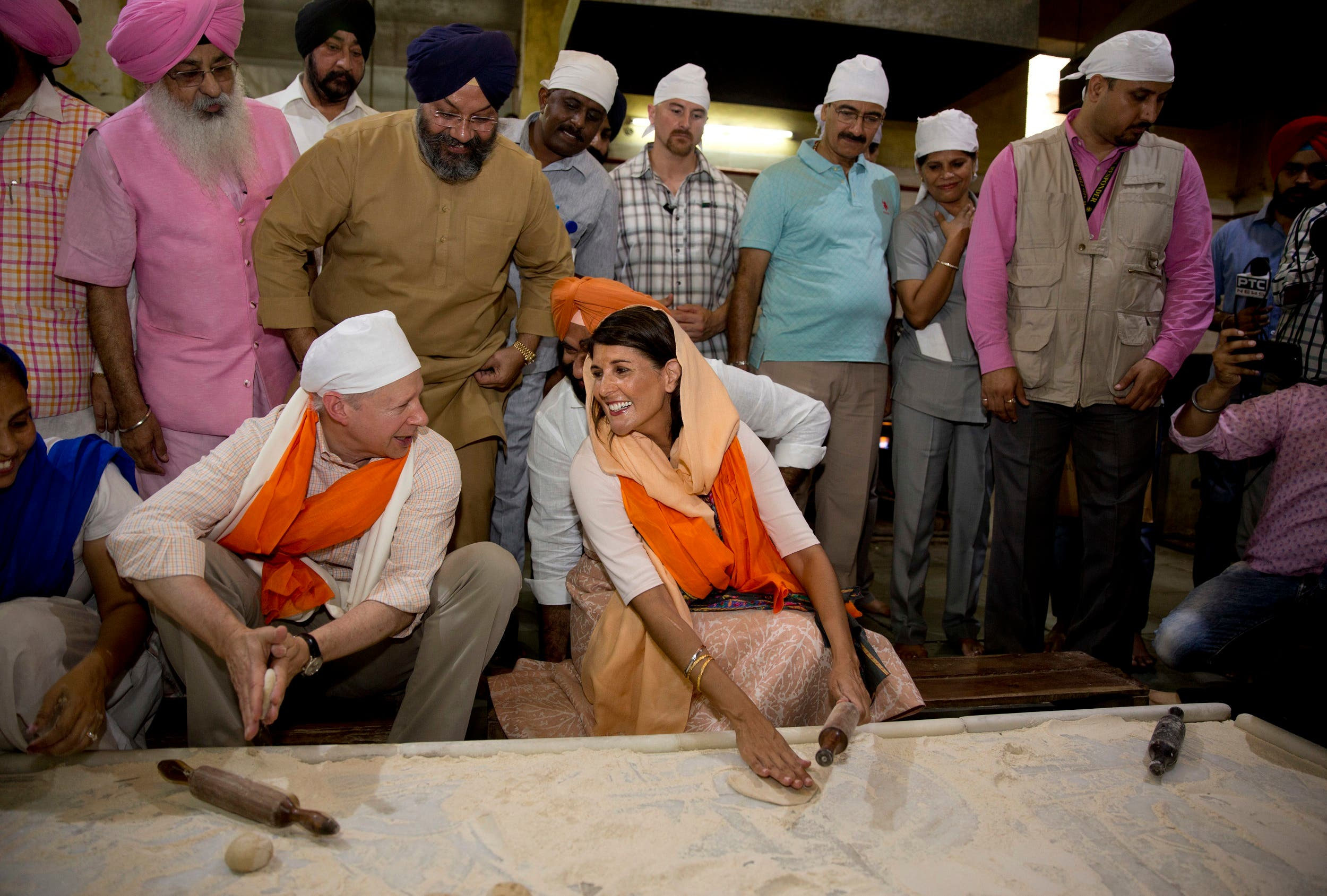 Nikki Haley talks with US ambassador to India Kenneth I. Juster while they try their hands on making Indian bread during their visit to a Gurdwara Sis Ganj Sahib, a Sikh temple, in New Delhi, on June 28, 2018. (AP)