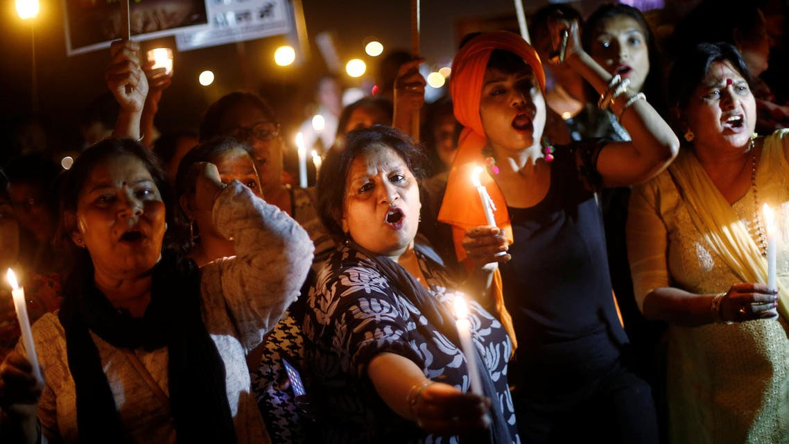 Women hold candles as they shout slogans during a protest against the rape of a 10-year-old girl, in the outskirts of Delhi on April 25, 2018. (Reuters)
