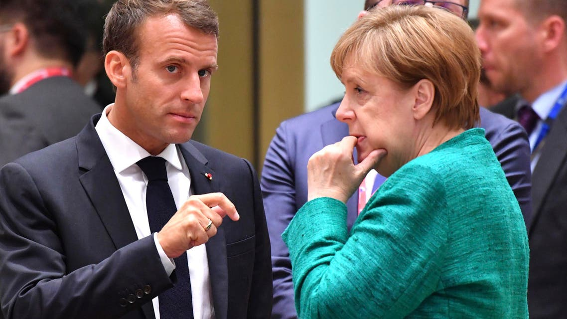 French President Emmanuel Macron, left, speaks with German Chancellor Angela Merkel during a round table meeting at an EU summit in Brussels, Thursday, June 28, 2018. AP