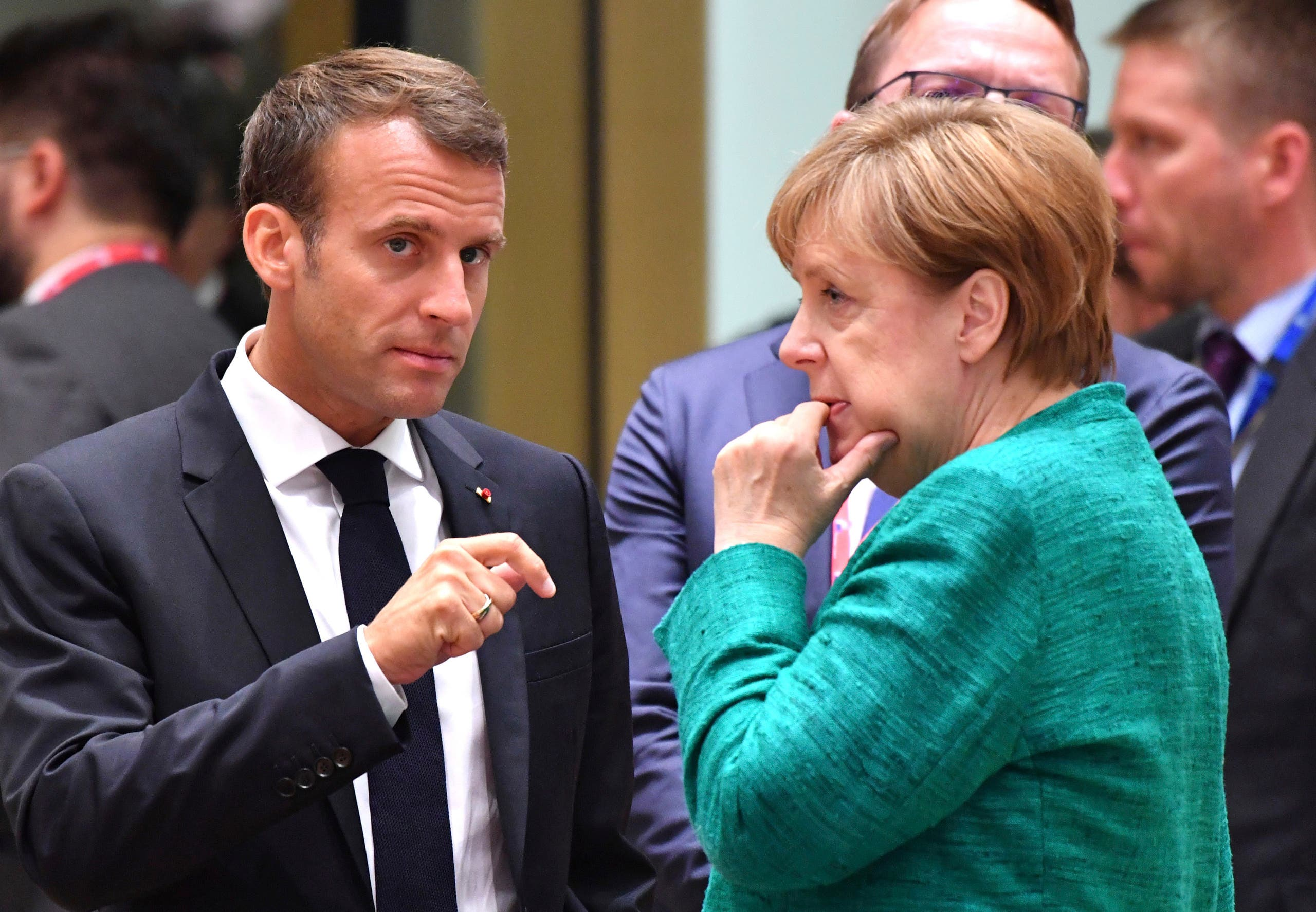 French President Emmanuel Macron, left, speaks with German Chancellor Angela Merkel during a round table meeting at an EU summit in Brussels, Thursday, June 28, 2018.