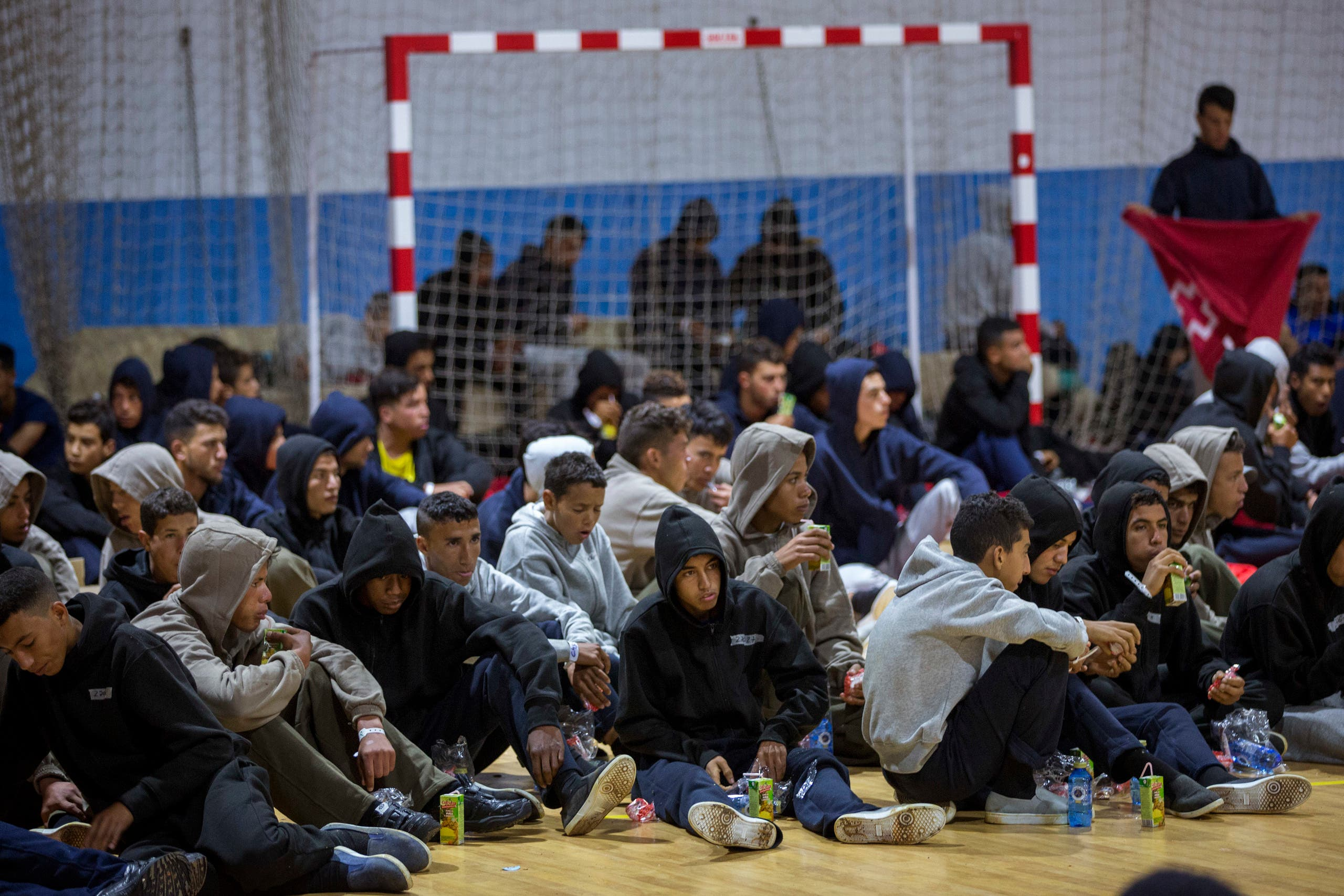 Moroccan migrants rest at a makeshift emergency center at Barbate's municipal sports center, in the south of Spain, after being rescued by Spain's Maritime Rescue Service in the Strait of Gibraltar, Thursday, June 28, 2018. (AP)
