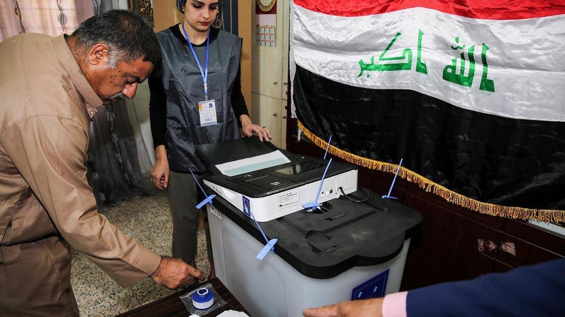 An Iraqi voter dips his finger in ink before casting his ballot at a poll station in the capital Baghdad's Karrada district on May 12, 2018. (AFP)