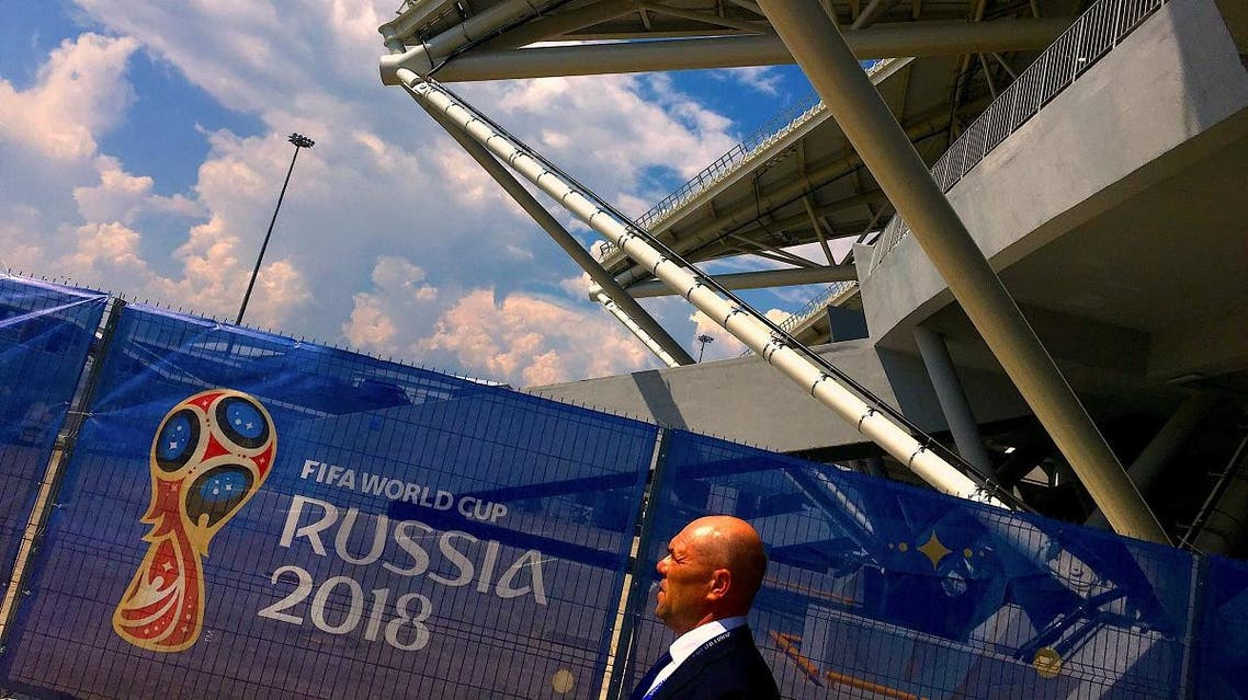 A security guard walks past a fence displaying a FIFA World Cup banner at Samara Stadium in Russia. (Reuters)