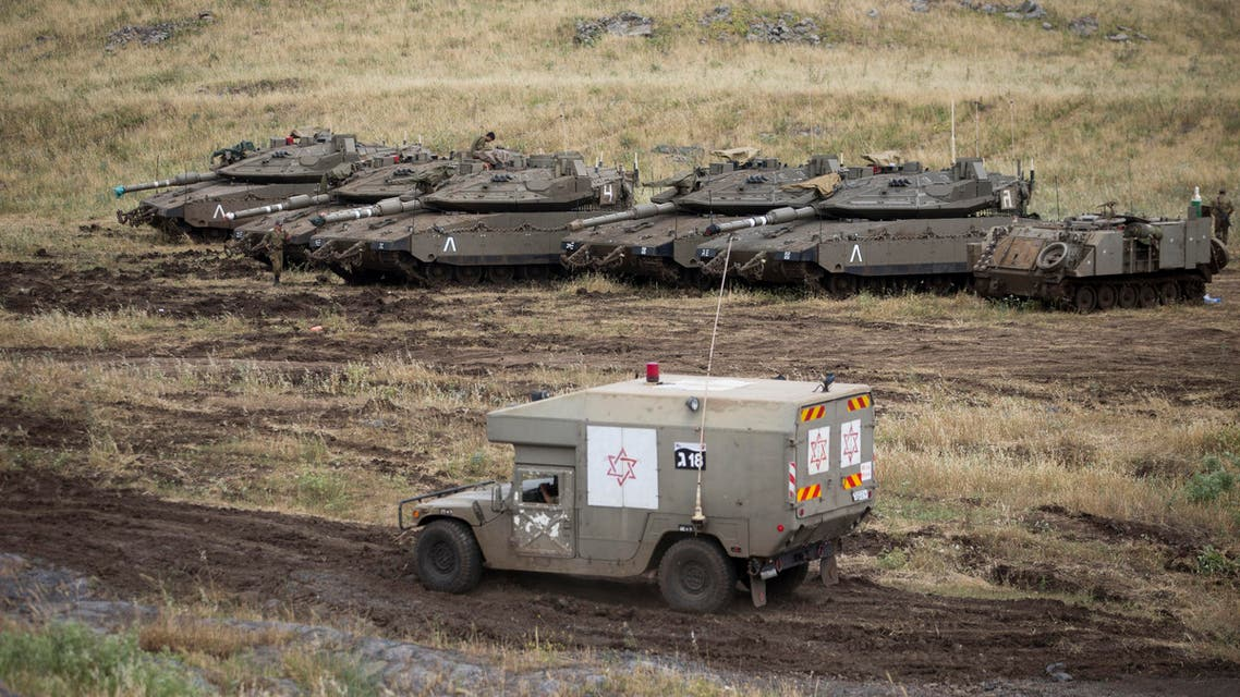 An Israeli military ambulance drives past tanks in the Israeli-controlled Golan Heights, near the border with Syria. (AP)