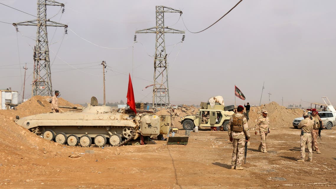Iraqi forces stand guard near the al-Qaim border crossing between Syria and Iraq on November 8, 2017. Iraq's authorities are now battling the final pockets of jihadists in their last footholds around the town of Al-Qaim, and Syrian troops are also approaching, hemming them in on their side of the frontier.