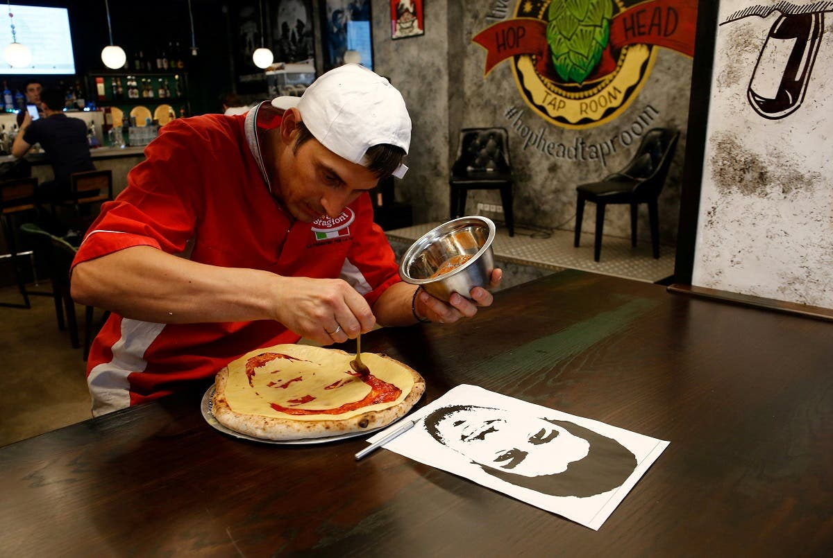 Cook Valery Maksimchik prepares a pizza decorated with a portrait of Uruguay's Luis Suarez at the Hop Head cafe in St. Petersburg. (Reuters)