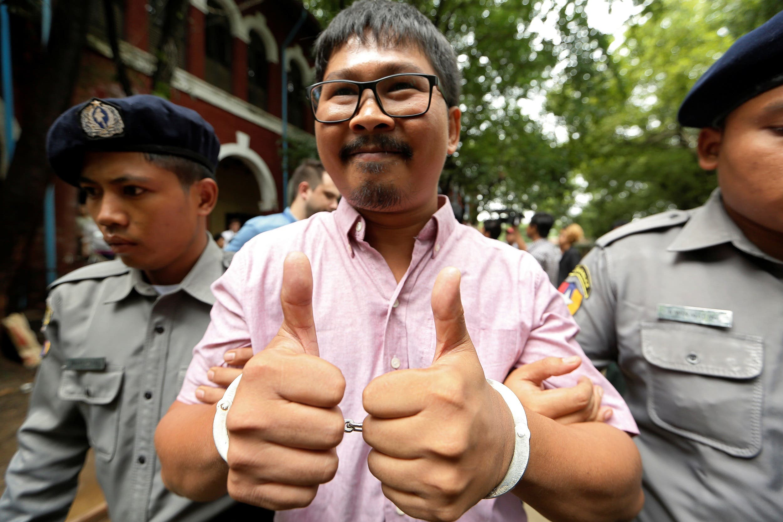 Detained Reuters journalist Wa Lone is escorted by police while leaving Insein court in Yangon, Myanmar July 2, 2018. REUTERS
