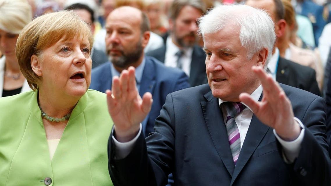 German Chancellor Merkel and German Interior minister Seehofer attend an event to commemorate victims of displacement in Berlin. (Reuters)