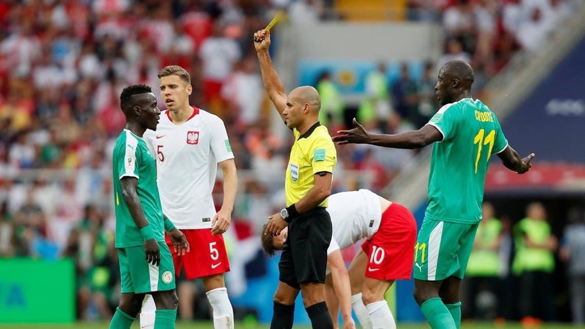 Senegal's Idrissa Gueye is shown a yellow card by referee Nawaf Shukralla. (Reuters)